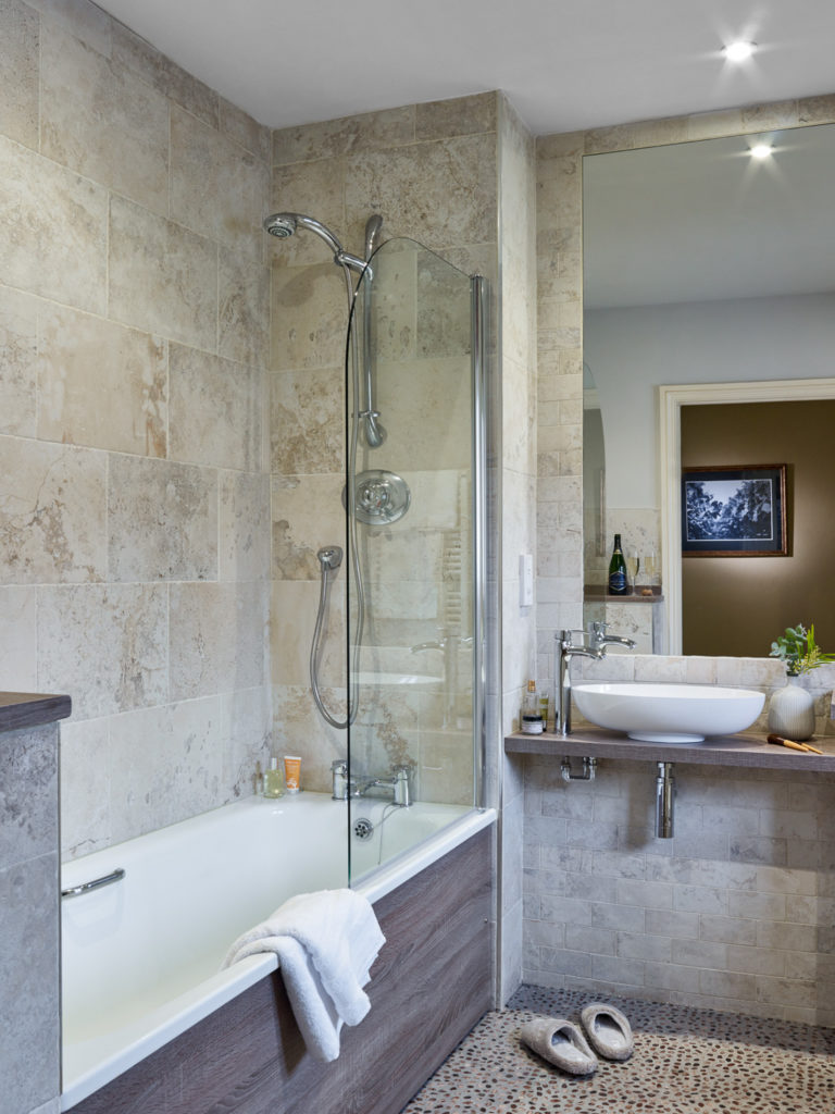 Bathroom with bath and shower over